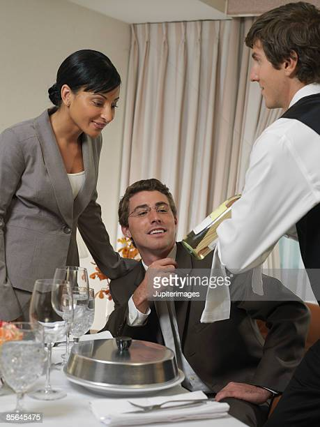 Waiter showing wine to couple