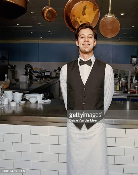 Waiter standing by kitchen, smiling, portrait