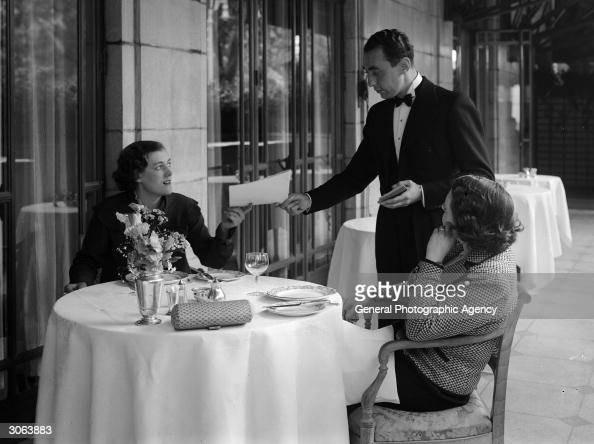 A waiter takes the order of two guests who are having a meal on the terrace at the Dorchester Hotel London
