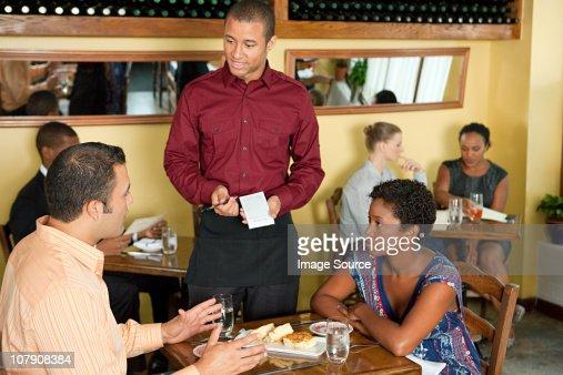 Waiter taking customer orders in restaurant