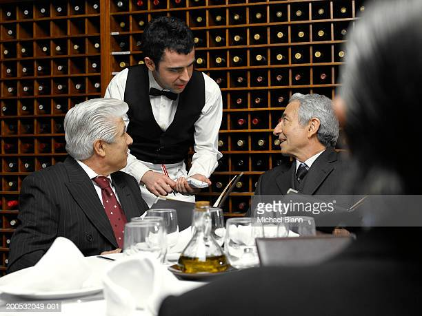 Waiter taking order from businessmen in restaurant