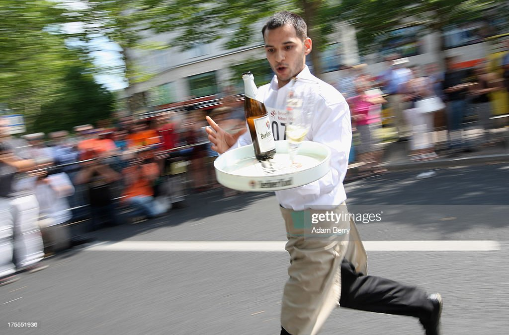 A waiter tries to save a beer bottle from tipping over as he runs during the Waiters' Derby (Kellner Derby in German) on August 4, 2013 in Berlin, Germany. At the annual event, brought back into existence in 2011 on the 125th anniversary of the Kurfuerstendamm (known locally as the Ku'damm), a main shopping thoroughfare, waiters, porters, cooks and bartenders run a 400-meter track while performing their regular occupational duties. The event was reinstated after a hiatus since the 1950s, when it was created to bring a sense of normal life back to Berlin after World War II under the Allies, a period in which gastronomical interest in the isolated Western part of the city suffered.