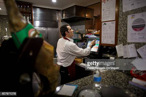 A waiter uses a cash till to charge customers for lunch during the day at Robin Hood restaurant on December 5 2016 in Madrid Spain Association...