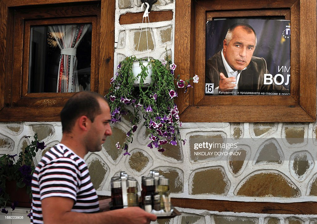 A waiter walks next to an election campaign poster of the former Bulgarian prime minister and leader of conservative GERB party on a window of a restaurant in Sofia on May 07, 2013. A winter of discontent in Bulgaria, when mass protests forced out the government, could give way to a spring of political deadlock and instability after elections Sunday in the EU's poorest country.