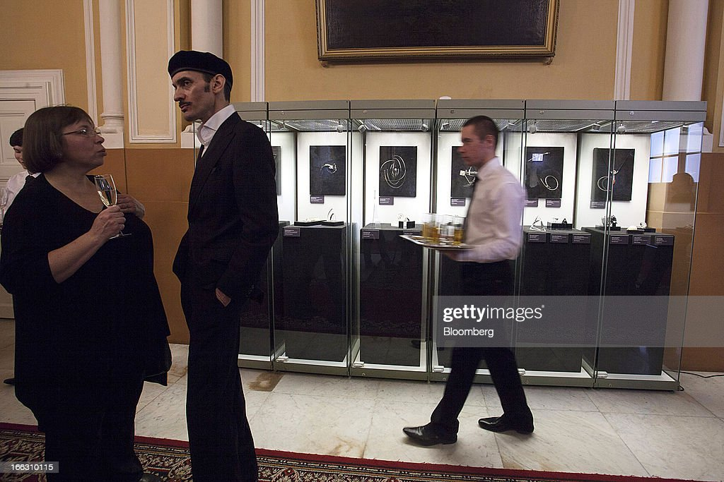 A waiter walks past a display of luxury diamond art jewelry exhibited at the Kremlin Museum by OAO Alrosa on the show's opening day in Moscow, Russia, on Thursday, April 11, 2013. OAO Alrosa may be valued at $9.4-10.8B when the Russian government looks to sell stake in the company in November, Vedomosti newspaper says, citing two unidentified bankers close to Goldman Sachs. Photographer: Alexander Zemlianichenko Jr./Bloomberg via Getty Images