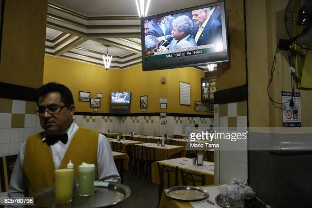 A waiter walks past as the congressional vote over President Michel Temer's bribery charge which could have suspended his presidency is played live...