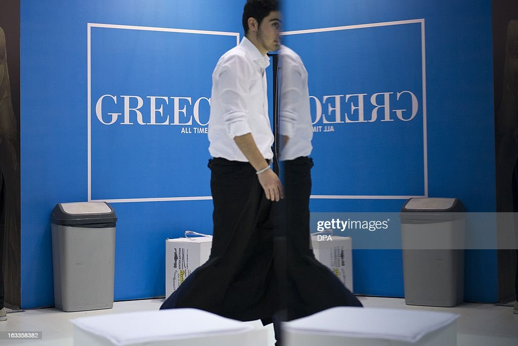 A waiter walks past the stand of Greece at the ITB Berlin tourism convention (Internationale Tourismus-Boerse) in Berlin on March 8, 2013. The ITB Berlin runs from March 6-10 and features Indonesia as its partner country for the event in 2013.