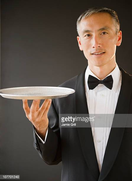 Waiter wearing bow tie and holding tray, studio shot