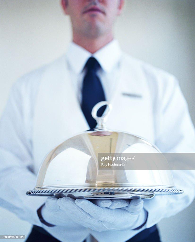 Waiter wearing white gloves, carrying silver platter : Stock Photo