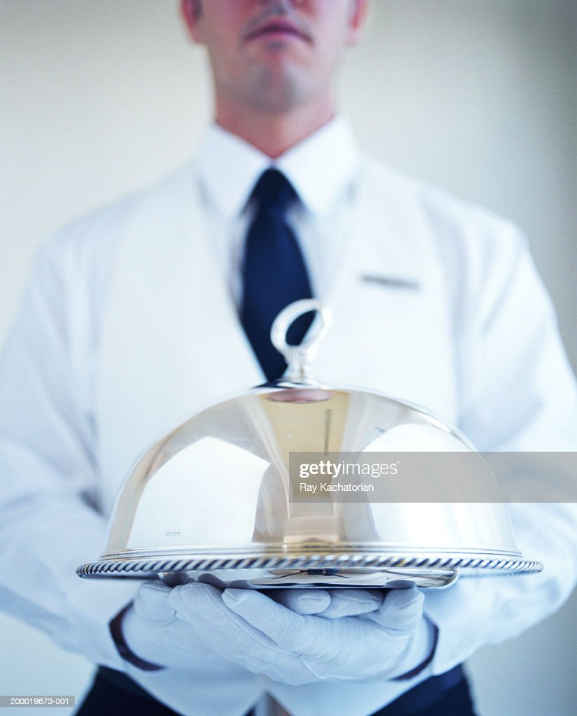 Waiter wearing white gloves, carrying silver platter