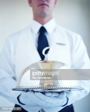 Waiter wearing white gloves, carrying silver platter : Stock Photo