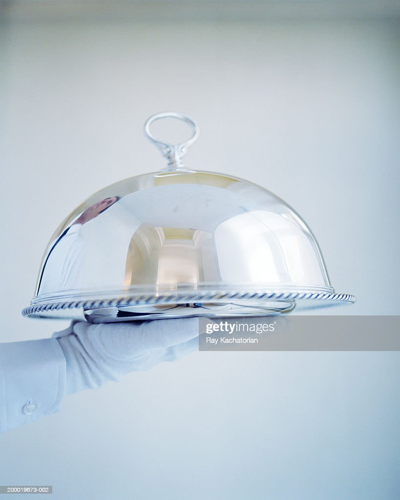 Waiter wearing white gloves holding silver tray : Stock Photo