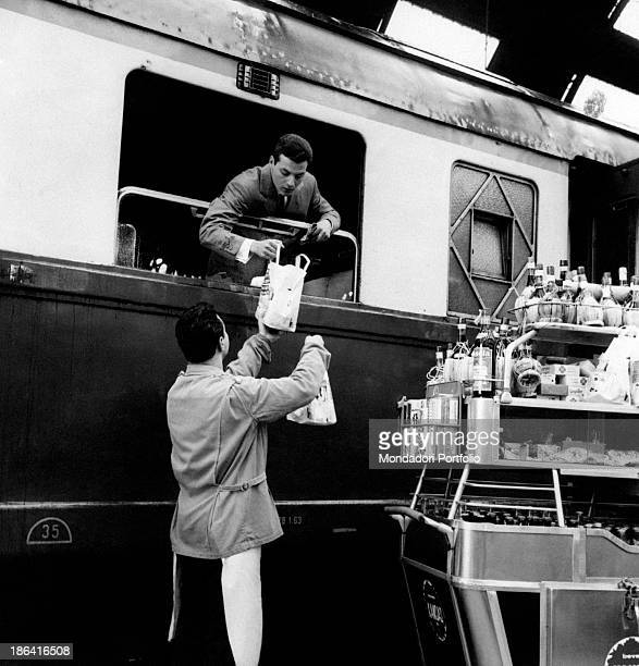A waiter with a cart delivering a sandwich to the passenger of a train May 1963