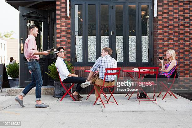 Waiter with coffee for people outside cafe