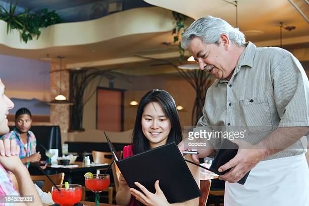 Waiter With Couple in Restaurant