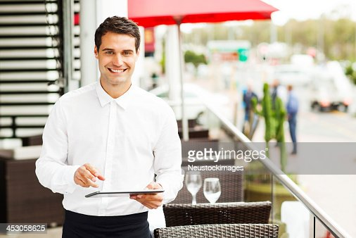 Waiter With Digital Tablet Smiling In Restaurant
