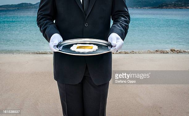 Waiter with gold credit card on the beach