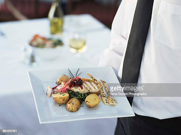 Waiter with gourmet chicken dish