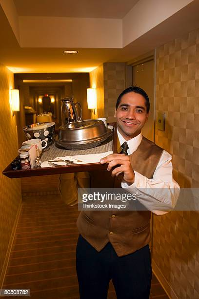 Waiter with room service in hallway