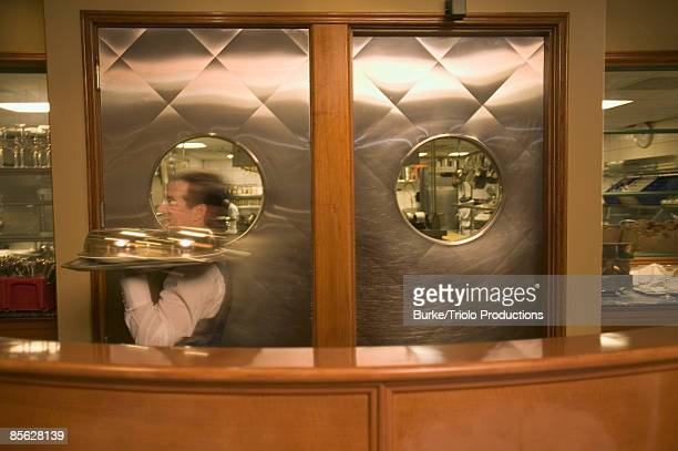 Waiter with tray in restaurant