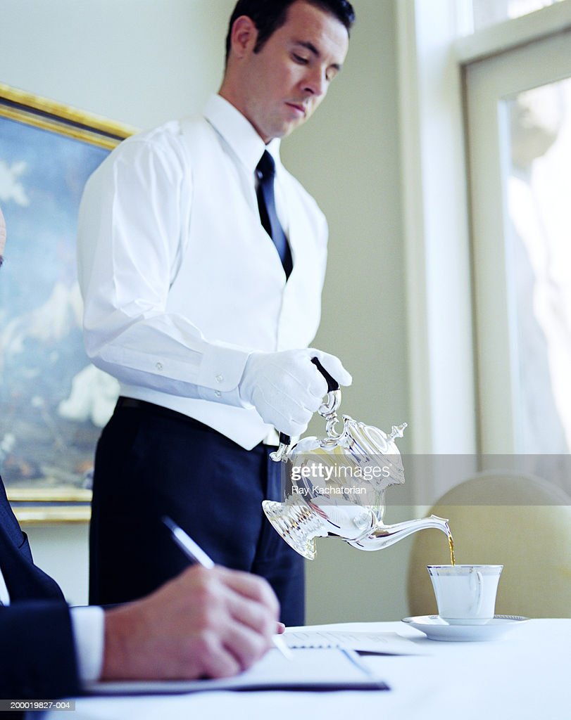 Waiter with white gloves pouring coffee : Stock Photo