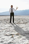 Waiter with wine glass in desert (low angle view)