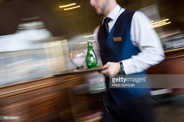 A waiter works in a French brasserie 'Le Train Bleu' on April 11 2013 in Paris AFP PHOTO / FRED DUFOUR