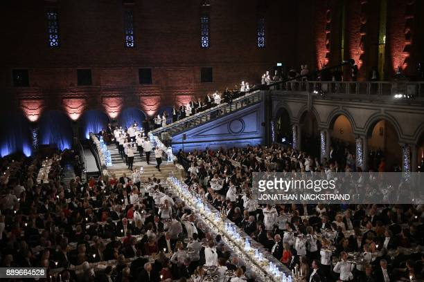 Waiters arrive to serve the dessert during the 2017 Nobel Banquet for the laureates in medicine chemistry physics literature and economics in...