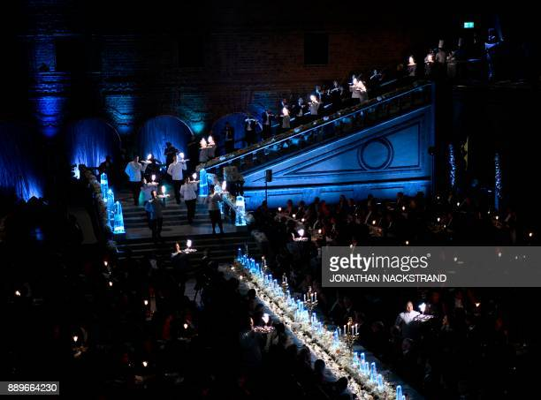 Waiters bring the dessert plates during the 2017 Nobel Banquet for the laureates in medicine chemistry physics literature and economics in Stockholm...
