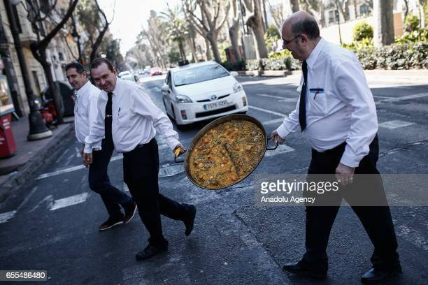 Waiters carries a 'La paella' in a street in Valencia Spain on March 20 2017 La Paella is a Valencian rice dish which has ancient roots Many...