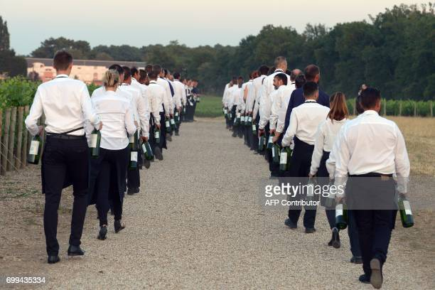 CORRECTION Waiters carry bottles of wine during the 65th 'Fete de la Fleur' at Chateau MalarticLagraviere in Leognan southwestern France on June 21...