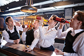 Group of young waiters in uniform standing at bar counter and contesting who drink beer faster in restaurant after hours