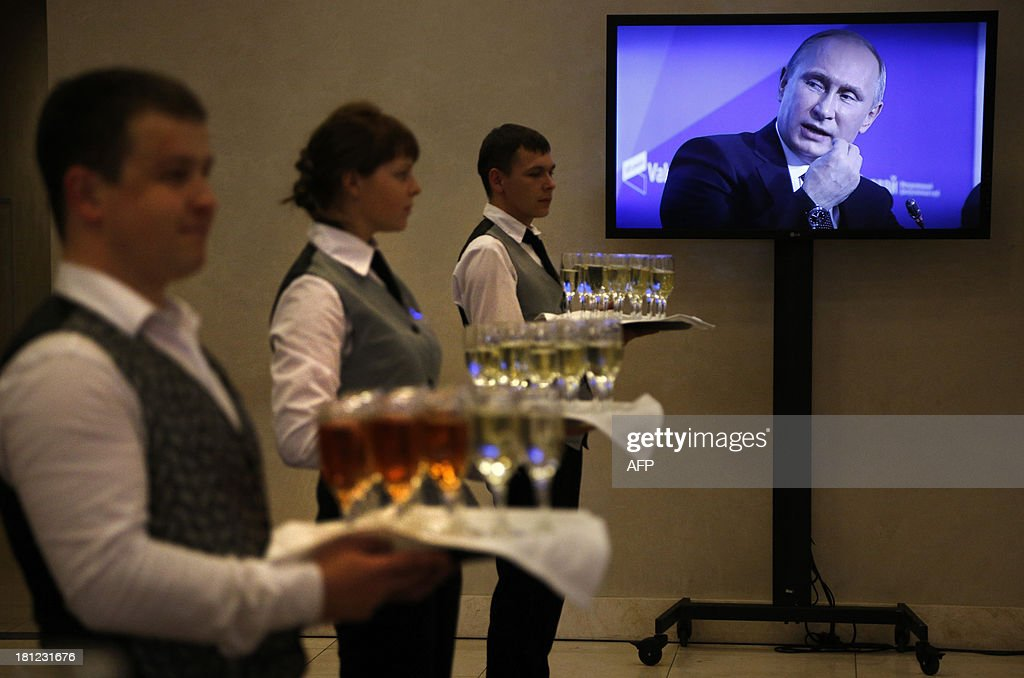 Waiters hold trays of champagne ready for a reception while Russia's President Vladimir Putin is seen on a TV screen as he speaks during the final plenary meeting of the 'Valdai' International Discussion Club members in the Russian town of Valday some 360 kilometers northwest of Moscow, on September 19, 2013. Putin said yesterday that he might run for a fourth term in the Kremlin, raising the possibility that he could lead Russia until 2024.