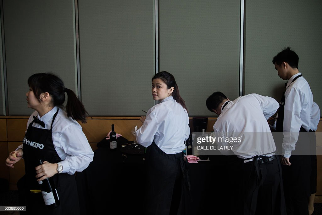 Waiters open wine bottles during a tasting event at Vinexpo in Hong Kong on May 24, 2016. The international wine and spirits exhibition runs from May 24 to 26. / AFP / DALE