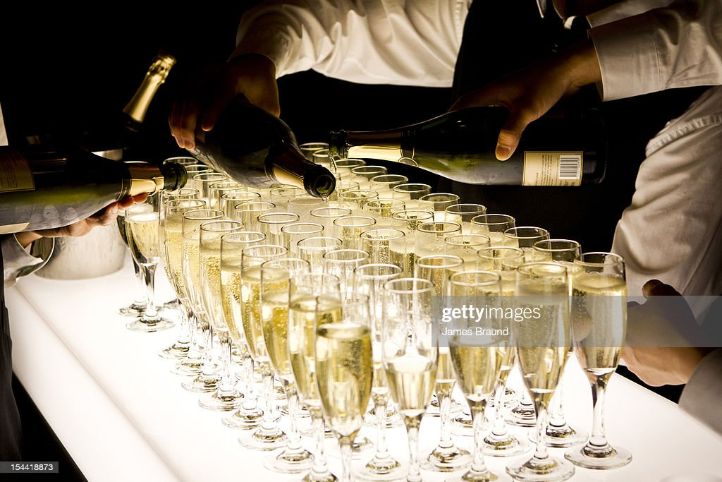 Waiters pour champagne into glasses : Stock Photo