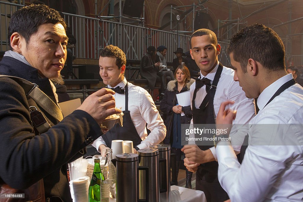 Waiters provide guests with hot drinks and cakes prior to the Lanvin Men Autumn / Winter 2013 show at Ecole Nationale Superieure Des Beaux-Arts as part of Paris Fashion Week on January 20, 2013 in Paris, France.