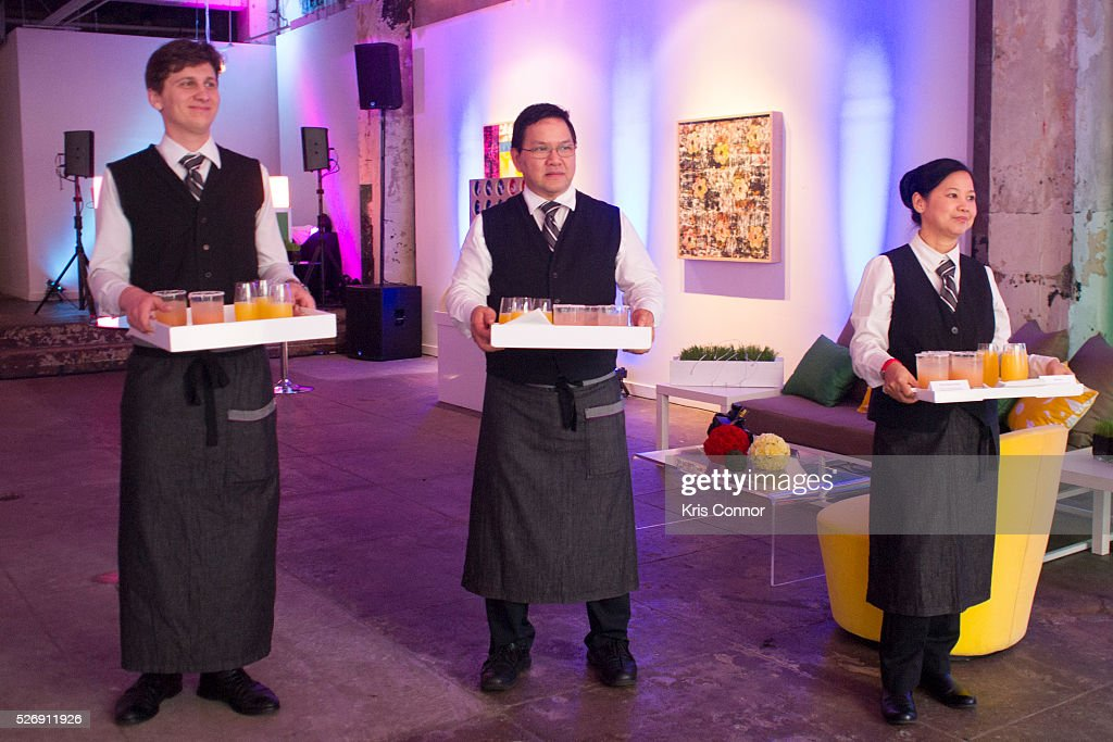Waiters serve cocktails during the 2016 CNN Correspondents' Brunch at the Longview gallery in Washington, DC on May 1, 2016.