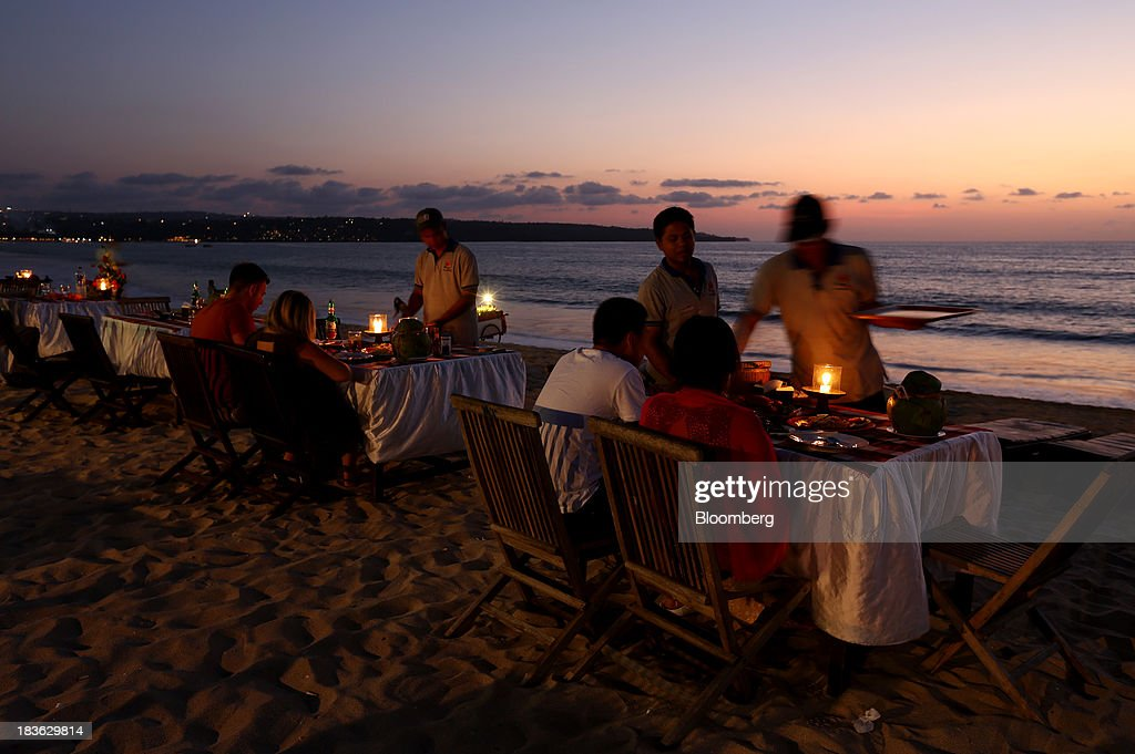 Waiters serve customers at a beachside restaurant at dusk in Jimbaran, Bali, Indonesia, on Saturday, Oct. 5, 2013. Indonesia's central bank kept its key interest rate unchanged after its most aggressive tightening cycle in almost eight years as inflation pressure eased. Photographer: SeongJoon Cho/Bloomberg via Getty Images