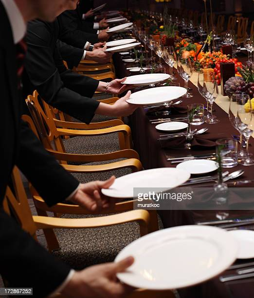 Waiters setting a table in a fancy restaurant