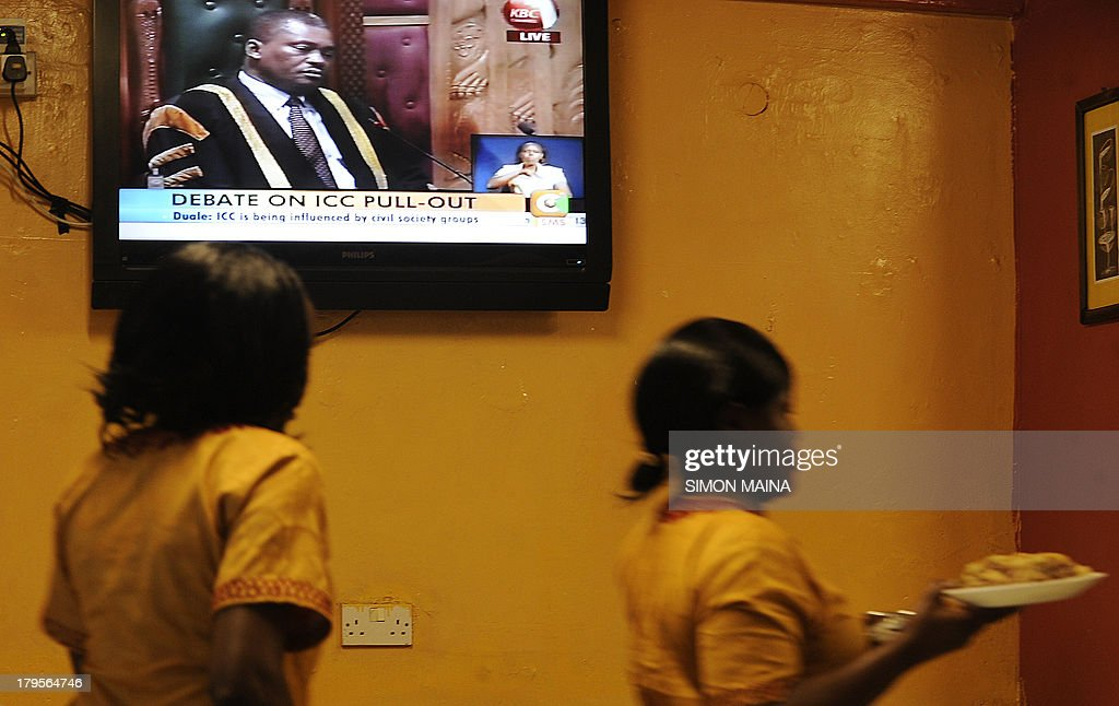 Waitesses serve food at a restaurant in Nairobi on September 5,2013 as local televsion broadcasts live proceedings on parliament disccussion on pulling out of the International Criminal Court (ICC). Kenyan lawmakers on September 5 began debating whether the country should pull out of the ICC, in an angry snub to The Hague-based tribunal ahead of next week's trial of Vice President William Ruto. Ruto on September 10 will be in The Hague to face three counts of crimes against humanity for allegedly organizing 2007-2008 post-election unrest that killed at least 1,100 people and displaced more than 600,000. His trial comes about two months ahead of that of President Uhuru Kenyatta, who faces five charges of crimes against humanity, including murder, rape, persecution and deportation.