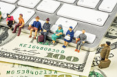 business concept, closeup of miniature figurine of people sitting on the edge of keyboard and waiting for money / wages