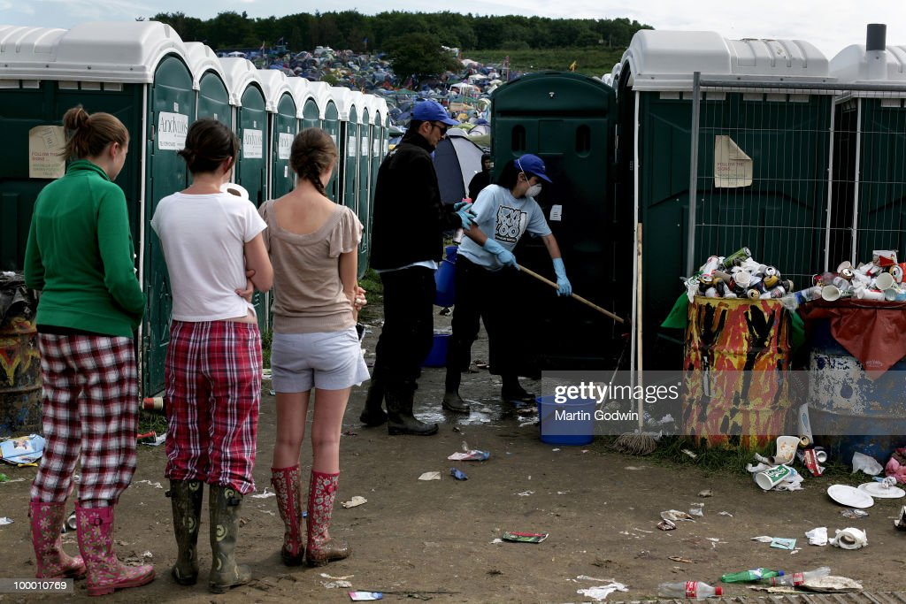 Waiting for toilets, Sunday morning in pyjamas, while cleaners, with face masks and gloves, clean out the porta loos by overflowing rubbish bin at Glastonbury, 28th June 2009.