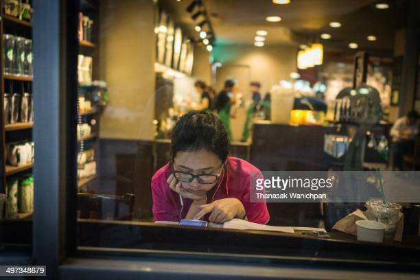 Waiting her friend and playing the internet on her smart phone at coffee shop
