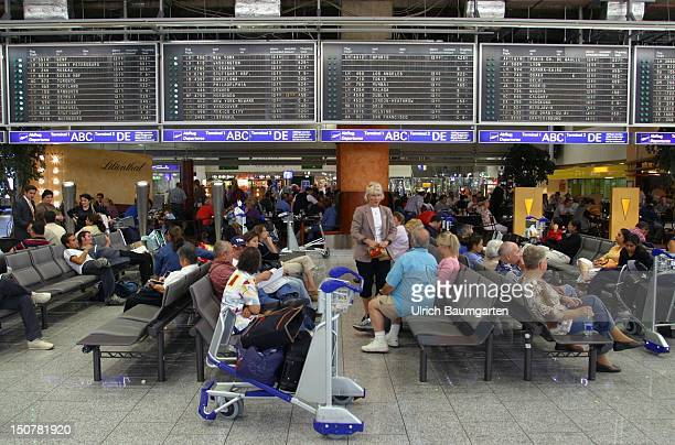 Waiting passengers are sitting in the departure lounge of Frankfurt Airport