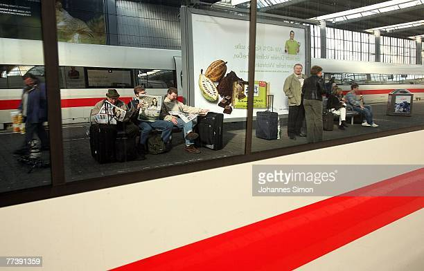 Waiting passengers of the German rail carrier Deutsche Bahn are reflected in the window of an ICE train at Hauptbahnhof Main Station on October 18...