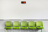 A bank of five green plastic seats against a neutral wall with a digital clock.