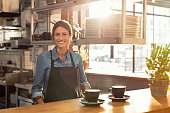 Smiling waitress wearing black apron standing behind counter in cafeteria and looking at camera. Mature woman serving two cups of hot coffee to customer in cafeteria. Small business and entrepreneur c