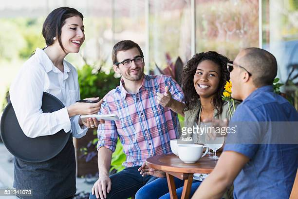Camarera en la cafetería en la acera con los clientes