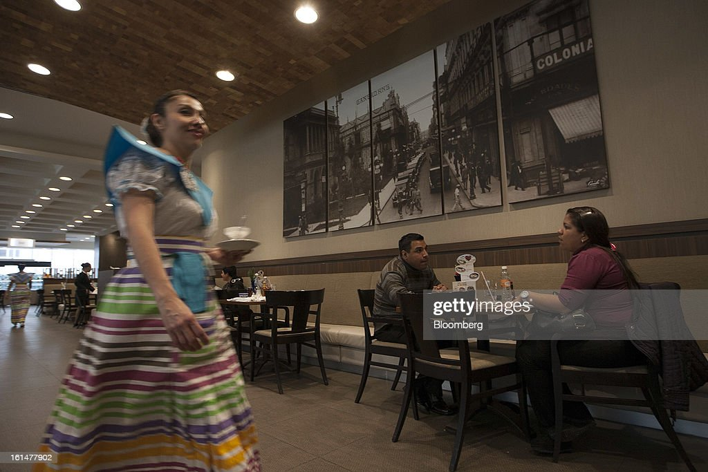 A waitress brings a beverage to a customer at a Grupo Sanborns SAB cafe in the Plaza Carso development in Mexico City, Mexico, on Friday, Feb. 8, 2013. Grupo Sanborns SAB, the retailer controlled by Mexican billionaire Carlos Slim, raised 10.5 billion pesos ($825 million) in an initial public offering (IPO) last week and the total could climb to 12.1 billion pesos including an overallotment option for underwriters. Photographer: Susana Gonzalez/Bloomberg via Getty Images