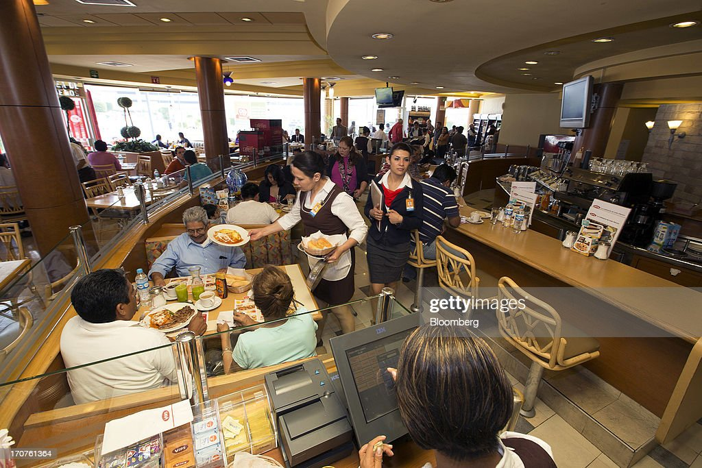 A waitress brings customers a food order at a Vips restaurant in the El Toreo neighborhood of Mexico City, Mexico, on Monday, June 17, 2013. Wal-Mart de Mexico SAB de CV, known as Walmex, is considering offers to sell its restaurant division, which includes the Vips, El Porton, Ragazzi and La Finca brands. Photographer: Susana Gonzalez/Bloomberg via Getty Images